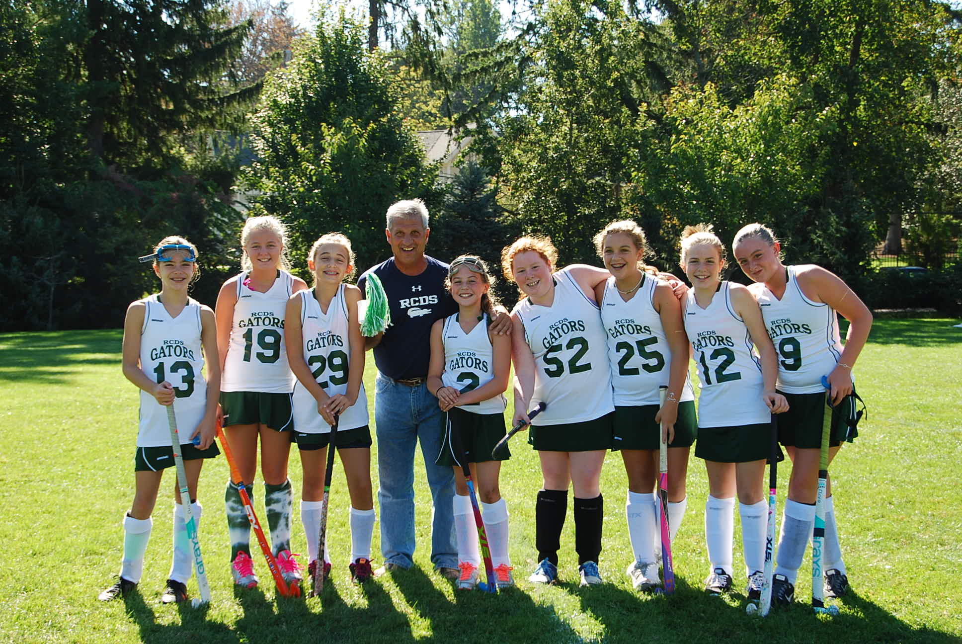 FIeld hockey players with a coach