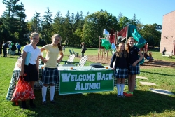 Three students with Welcome Alumni banner