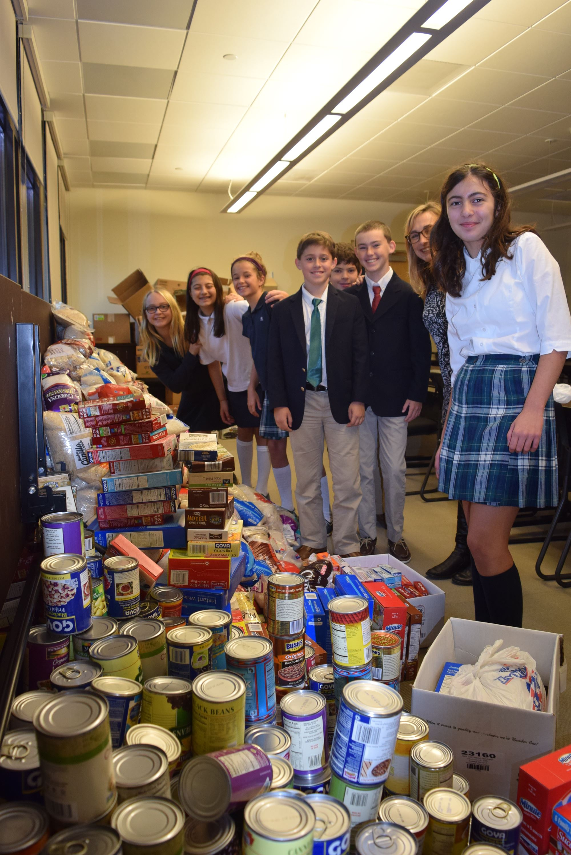 Sixth graders pose with canned goods for a food drive